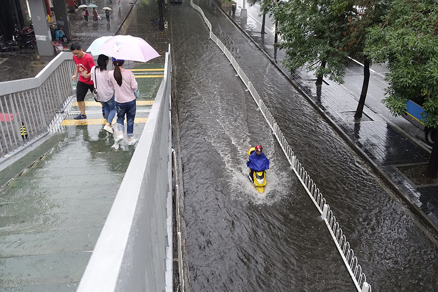 Downpour floods streets in Beijing, turns down summer heat