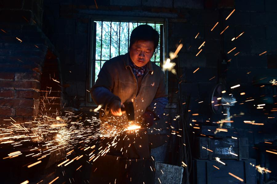 Yu Songtao makes a pair of scissors in Houshan village under Dingjiaqiao town of Jingxian county, East China's Anhui province, Nov 17, 2016. [Photo/Xinhua]<br/>