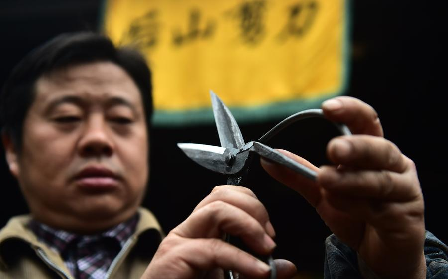 Yu Songtao checks a pair of scissors he made in Houshan village under Dingjiaqiao town of Jingxian county, East China's Anhui province, Nov 17, 2016. [Photo/Xinhua]<br/>
