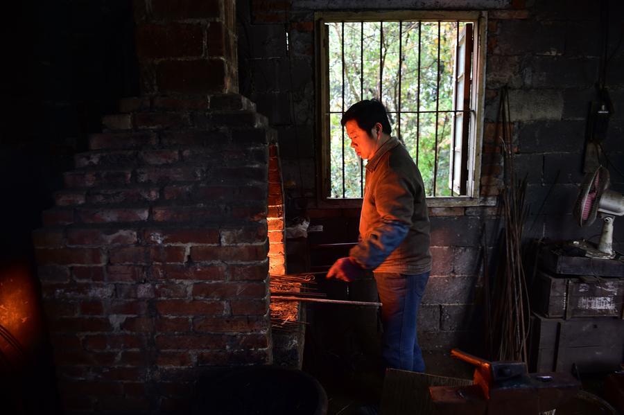 Yu Songtao heats the rebar for making scissors in Houshan village under Dingjiaqiao town of Jingxian county, East China's Anhui province, Nov 17, 2016. [Photo/Xinhua]<br/>