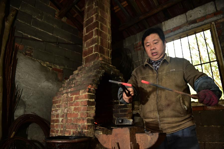 Yu Songtao cuts the rebar for making scissors in Houshan village under Dingjiaqiao town of Jingxian county, East China's Anhui province, Nov 17, 2016. [Photo/Xinhua]<br/>