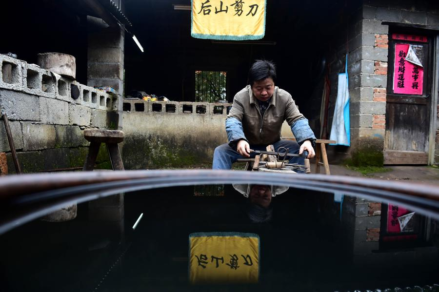 Yu Songtao polishes a pair of scissors in village under Dingjiaqiao town of Jingxian county, East China's Anhui province, Nov 17, 2016. Yu Songtao, the inheritor of the technique of scissors production in Houshan village, has been making scissors for 35 years since he was 15 years old. There are over 80 procedures in making a pair of scissors. Yu can only make a dozen of them every day because of the complicated crafts. He wishes that more people will learn about the technique so that this intangible cultural heritage will be carried on. [Photo/Xinhua]<br/>